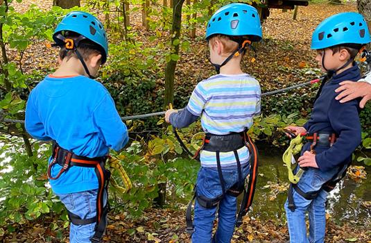 Kinder beim Klettern im Wald