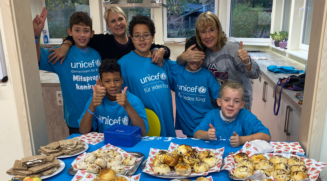 Kinder mit Unicef-Shirts vor Buffet